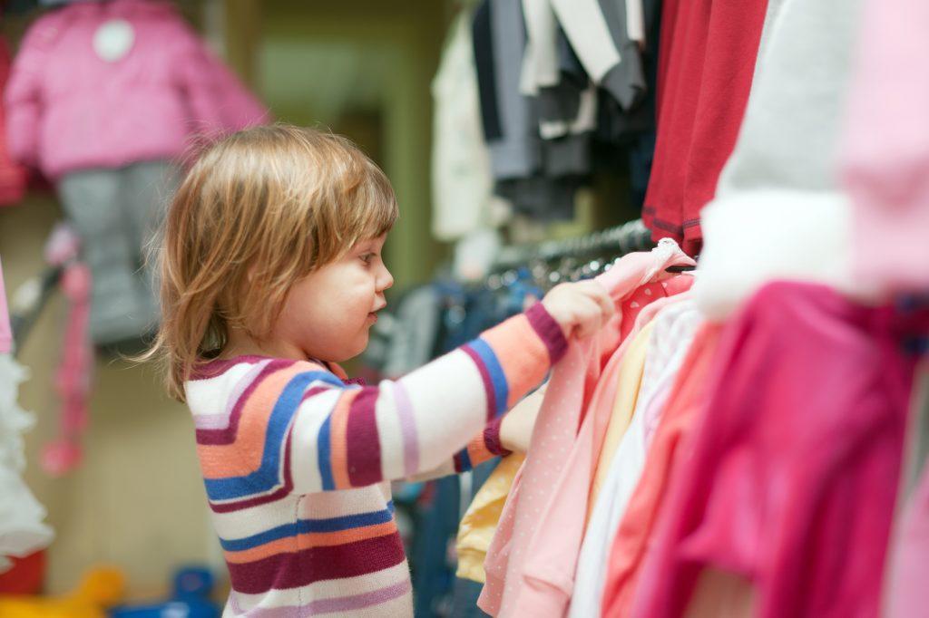 baby girl  chooses clothes at shop